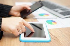 A mulher de negócios ocupada está trabalhando no tablet pc e na utilização espertos Fotografia de Stock