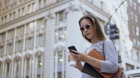 Mulher de negócios ocupada nova nos óculos de sol que guardam os originais, usando o smartphone e bebendo o café na rua video estoque