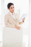 Mulher de negócios olhando de sobrancelhas franzidas que está atrás de sua cadeira que guarda a tabuleta Fotos de Stock Royalty Free