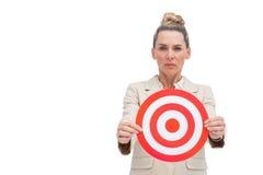 Mulher de negócios olhando de sobrancelhas franzidas que guardara o alvo Imagem de Stock