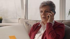 Mulher de negócios pensativa que fala no telefone na zona da sala de estar do escritório vídeos de arquivo