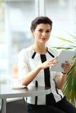 Mulher de negócios pensativa que lê um artigo no tablet pc imagens de stock royalty free