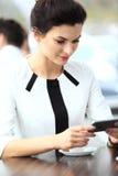 Mulher de negócios pensativa que lê um artigo no tablet pc imagem de stock
