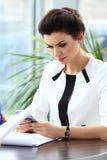 Mulher de negócios pensativa que lê um artigo no tablet pc fotografia de stock