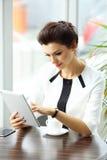 Mulher de negócios pensativa que lê um artigo no tablet pc imagens de stock