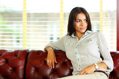 Mulher de negócios pensativa que senta-se no sofá Fotografia de Stock Royalty Free