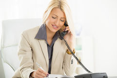 Mulher de negócios Phoning In Office fotografia de stock royalty free