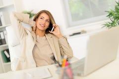 Mulher de negócios Phoning In Office imagens de stock royalty free