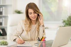 Mulher de negócios Phoning In Office imagem de stock