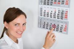 Mulher de negócios Placing Red Mark On Calendar Date Imagem de Stock Royalty Free