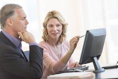 Mulher de negócios Pointing At Computer ao sentar-se com colega imagem de stock