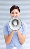 Mulher de negócios positiva que grita através de um megafone Fotos de Stock Royalty Free