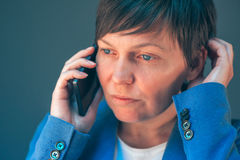 Mulher de negócios preocupada durante a conversação telefônica desagradável foto de stock