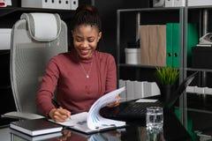 A mulher de negócios preta nova espetacular assina documentos na tabela no escritório imagem de stock royalty free