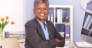 Mulher de negócios preta que senta-se no sorriso da mesa Foto de Stock Royalty Free