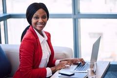 Mulher de negócios preta que sorri na câmera quando assentado no sofá Imagem de Stock