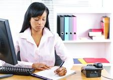 Mulher de negócios preta séria na mesa Foto de Stock