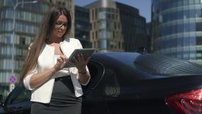 Mulher de negócios principal do banqueiro elegante que usa a tabuleta que está no fundo do carro e das construções filme