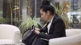 A mulher de negócios procura algo em seu saco filme