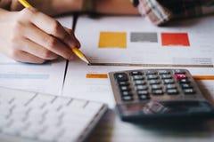 Mulher de negócios que analisa cartas do investimento com a calculadora para o fi fotografia de stock
