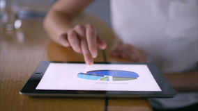 Mulher de negócios que analisa cartas financeiras na tabuleta digital video estoque