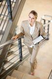 Mulher de negócios que anda acima das escadas Fotografia de Stock