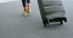 Mulher de negócios que anda com a mala de viagem no escritório 4k filme
