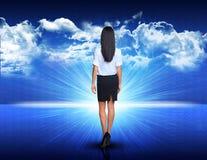 Mulher de negócios que anda contra a paisagem azul com Imagem de Stock