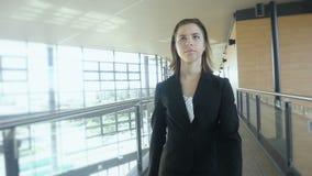 Mulher de negócios que anda no movimento lento do prédio de escritórios filme
