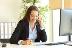 Mulher de negócios que chama o telefone e que toma notas Imagens de Stock