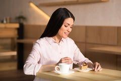 Mulher de negócios que come o bolo com café imagem de stock royalty free