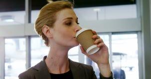 Mulher de negócios que come o café do copo descartável filme