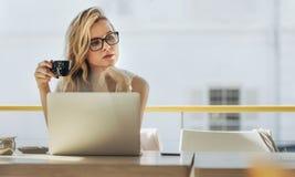 Mulher de negócios que come o café e que pensa no café fotos de stock royalty free