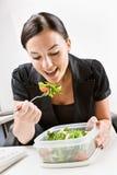 Mulher de negócios que come a salada na mesa Fotos de Stock Royalty Free