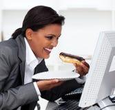 Mulher de negócios que come um eclair de chocolate Fotografia de Stock Royalty Free