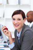 Mulher de negócios que come uma maçã no escritório Imagens de Stock Royalty Free