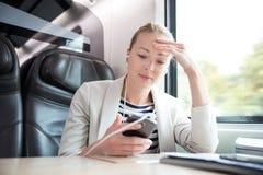 Mulher de negócios que comunica-se no telefone celular ao viajar pelo trem fotos de stock royalty free