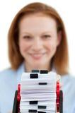 Mulher de negócios que consulta seu suporte do cartão Fotografia de Stock Royalty Free