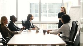 Mulher de negócios que dá a apresentação aos colegas multi-étnicos na reunião na sala de reuniões vídeos de arquivo