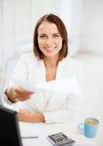 Mulher de negócios que dá papéis no escritório Fotografia de Stock Royalty Free