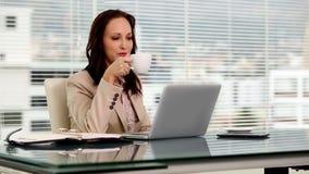 Mulher de negócios que datilografa em seu portátil filme