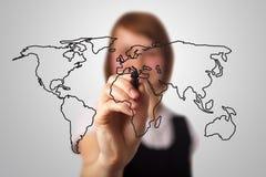 Mulher de negócios que desenha o mapa de mundo Fotografia de Stock