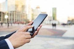 Mulher de negócios que envia mensagens com seu telefone esperto na frente de Imagem de Stock Royalty Free