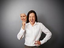 Mulher de negócios que esconde sua raiva atrás da máscara fotografia de stock royalty free