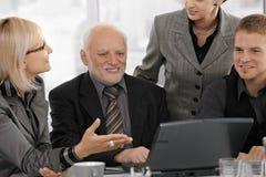 Mulher de negócios que explica o trabalho aos colegas Fotografia de Stock Royalty Free