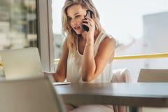 Mulher de negócios que fala com o cliente sobre o telefone no café fotos de stock royalty free