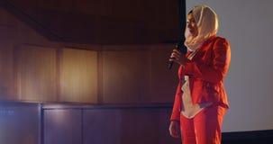 Mulher de negócios que fala na fase no auditório 4k video estoque