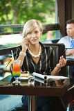 Mulher de negócios que fala no móbil no café Imagens de Stock Royalty Free