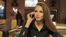 Mulher de negócios que fala no smartphone no café video estoque
