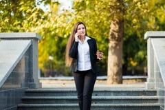 Mulher de negócios que fala no telefone ao andar exterior fotografia de stock royalty free
